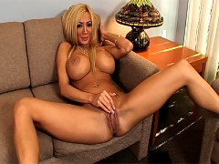 Busty blonde rubs pussy in on office couch